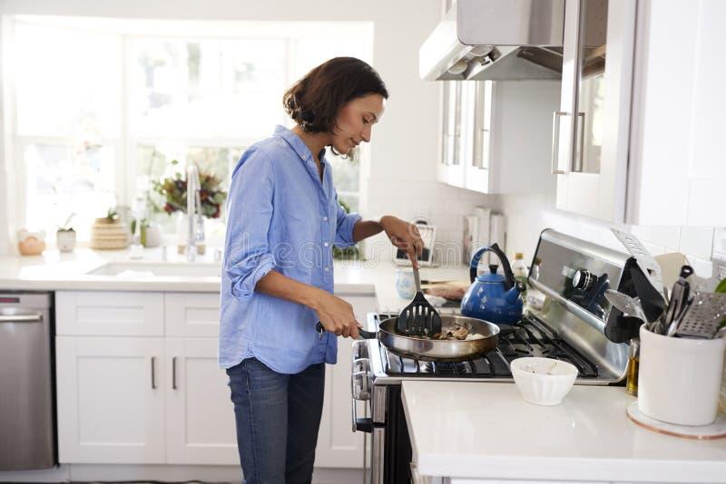 在滚刀的年轻妇女身分在烹调食物的厨房里使用小铲和煎锅,侧视图 免版税库存照片