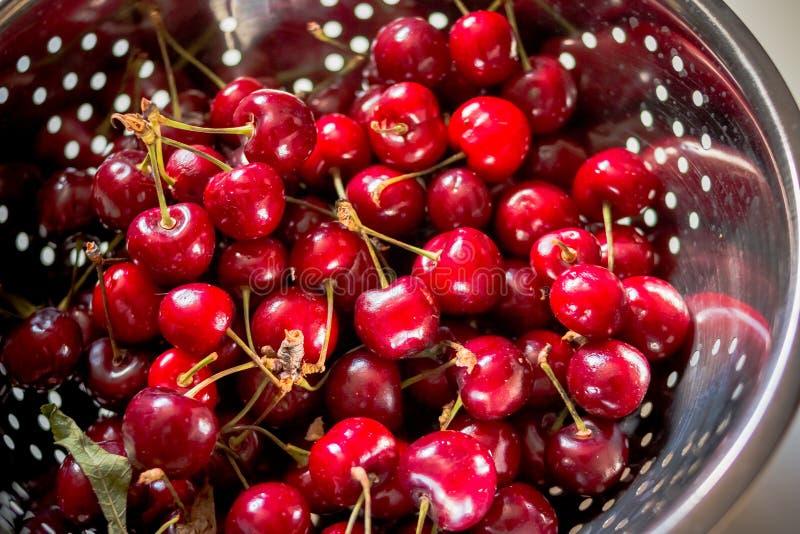 在滤锅的新鲜的成熟樱桃在晴朗的早晨 金属化过滤器用甜红色莓果和樱桃在木背景 免版税库存图片