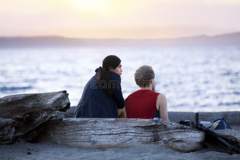 在漂流木头的年轻夫妇采伐谈话在海滩在日落 免版税库存照片