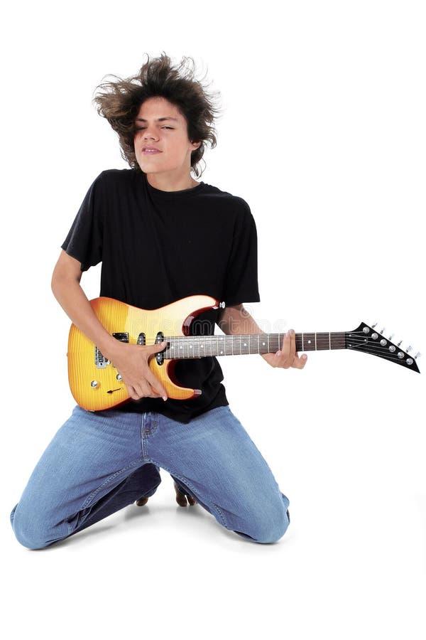 在演奏青少年的白色的赤足电吉他 免版税库存照片