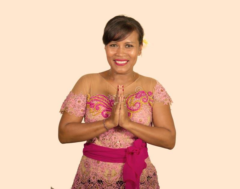 在演播室传统宗教仪式礼服微笑的快乐的美丽和愉快的印度尼西亚巴厘语妇女隔绝的 图库摄影