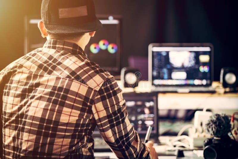 在演播室和用途膝上型计算机工作编辑录影镜头的他的美满的创作者 免版税图库摄影