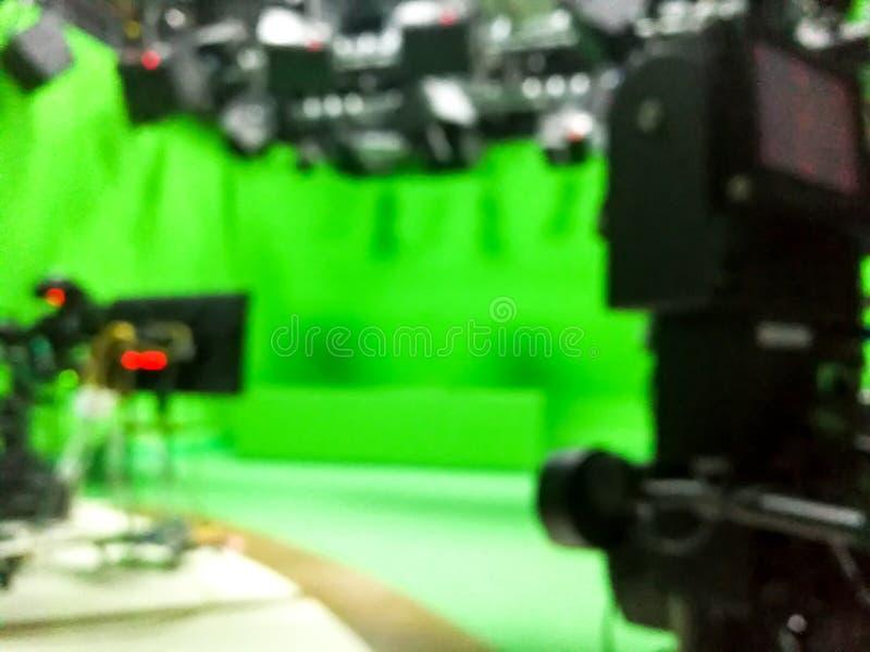 在演播室模糊的照片一台摄象机的一个电视赠送者一个绿色屏幕 库存照片