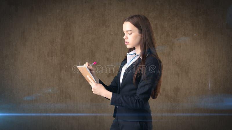 在演播室背景隔绝的她的组织者的严肃的确信的女实业家文字 免版税库存图片