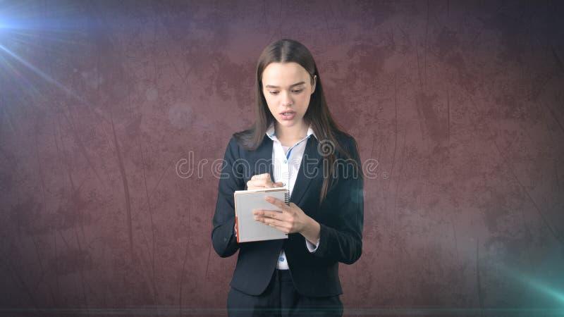 在演播室背景隔绝的她的组织者的严肃的确信的女实业家文字 库存照片