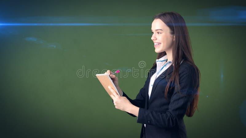 在演播室背景隔绝的她的组织者的友好的确信的女实业家文字 库存图片