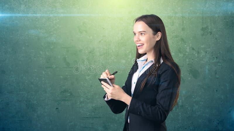 在演播室背景隔绝的她的组织者的友好的确信的微笑的女实业家文字 图库摄影