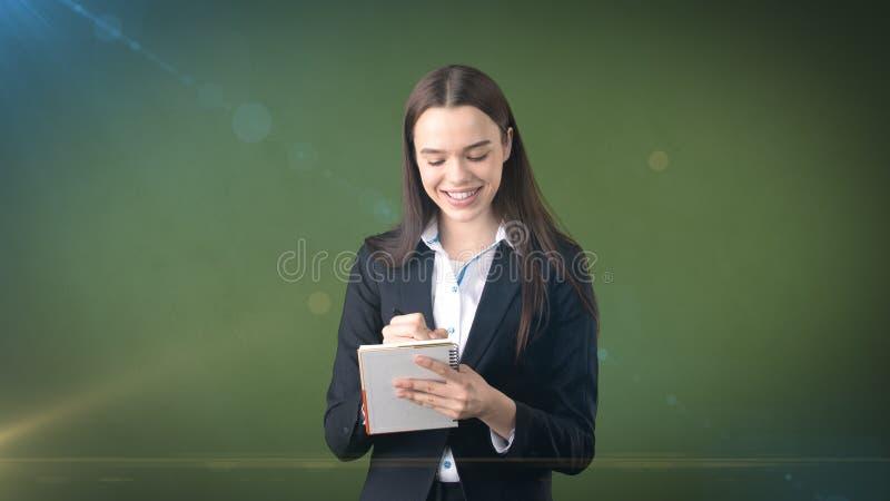 在演播室背景隔绝的她的组织者的友好的确信的微笑的女实业家文字 库存照片