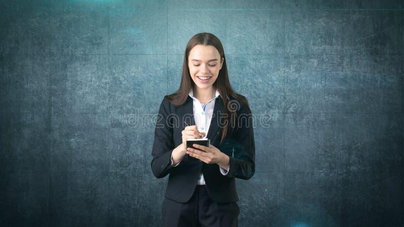 在演播室背景隔绝的她的组织者的友好的确信的微笑的女实业家文字 库存图片