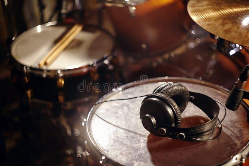 在演播室鼓的黑耳机 美丽的特写镜头概念录音室或音乐堂工具 音乐背景 免版税库存照片