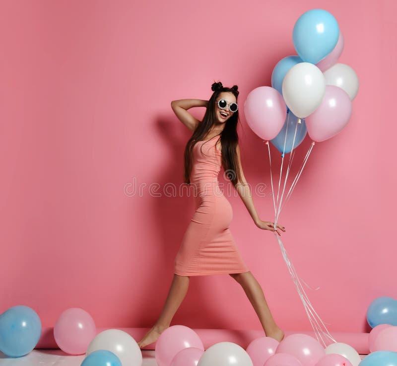 在演播室,广泛微笑和使用与蓝色和桃红色baloons的逗人喜爱的白肤金发的女孩身分特写镜头 图库摄影
