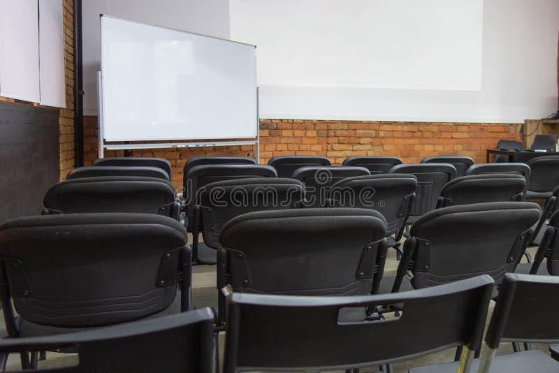在演示或研讨会前,白板和墙壁显示屏前排空椅子 教室或会议厅之前 库存照片