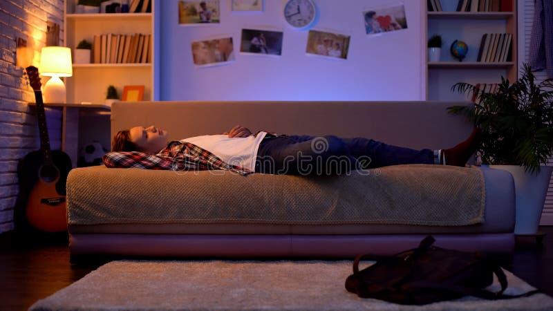 在演讲以后的疲倦的青少年的男生回家,躺下在长沙发,休息 免版税库存照片