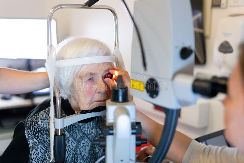 在激光手术期间的资深妇女在眼科学诊所 库存图片
