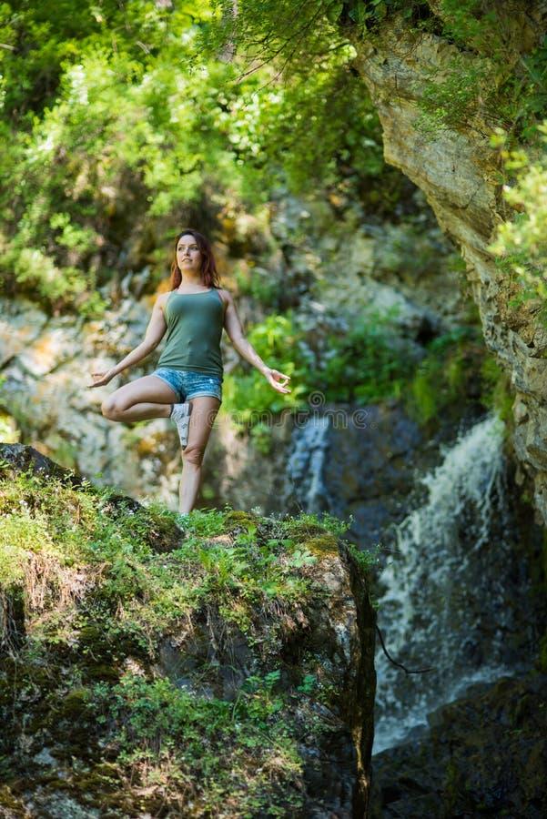 在瀑布做瑜伽的红发女人 一个女孩站在森林里树的姿势 库存照片