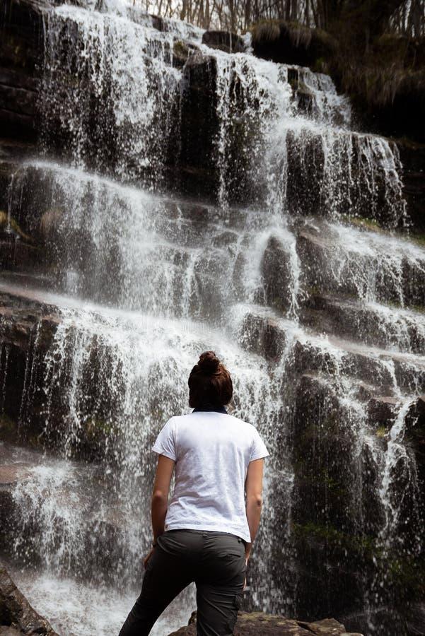 在瀑布前面的女孩身分 库存图片