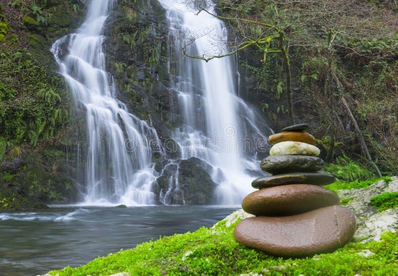 在瀑布前面的平衡的岩石禅宗堆 免版税图库摄影