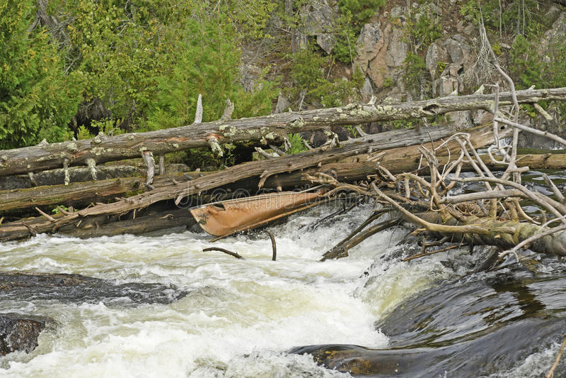 在瀑布的残破的独木舟 库存图片