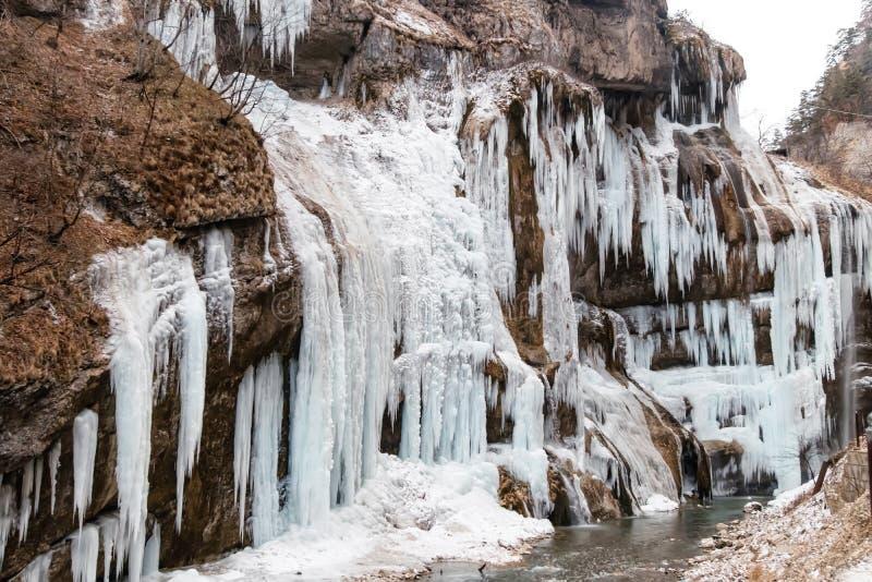 在瀑布站点的大冻结的冰柱在山区 图库摄影