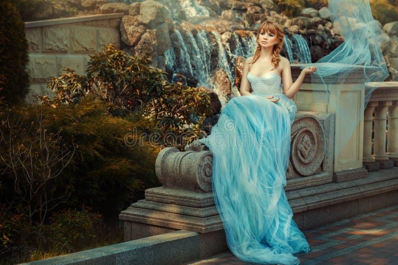 在瀑布附近的女孩在庭院里 免版税库存照片