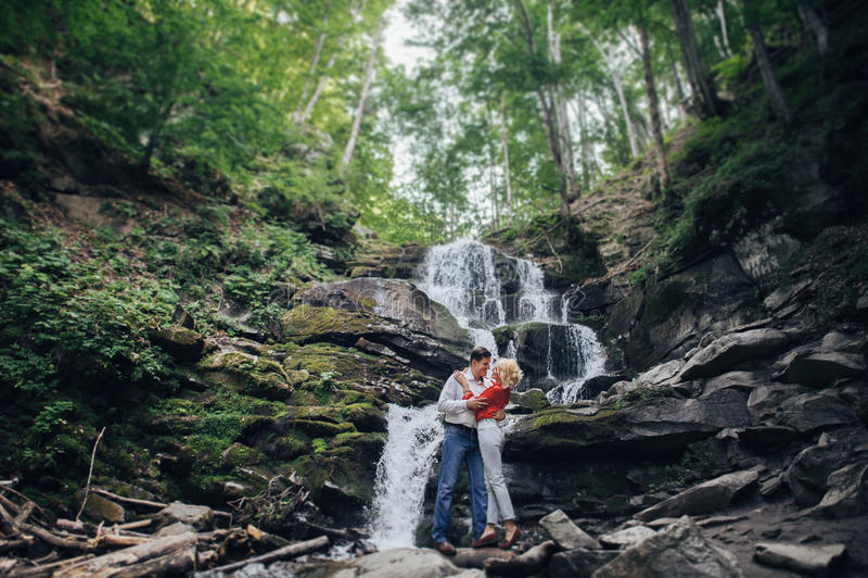 在瀑布附近的爱恋的夫妇在森林里 免版税库存照片
