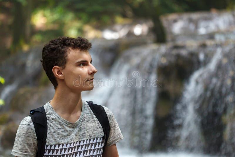 在瀑布附近的远足者男孩 图库摄影