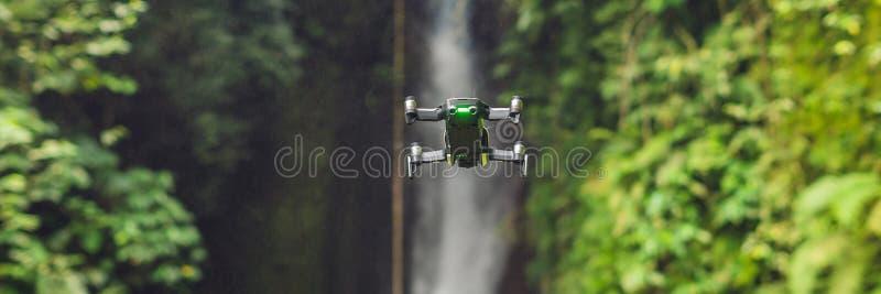 在瀑布Leke Leke巴厘岛印度尼西亚横幅附近的小的quadcopter飞行,长的格式 免版税库存图片