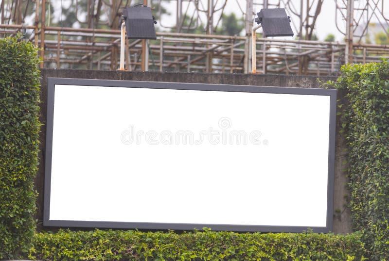 在灌木框架的空白的广告牌与斑点光 免版税图库摄影