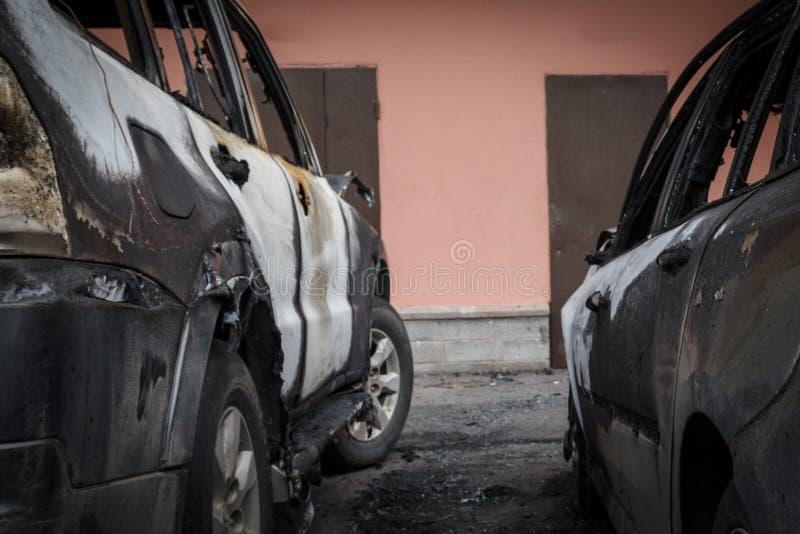 在火以后的两辆汽车 两部分地被烧在汽车下 从火的火在一辆汽车在别的被投掷了 库存照片