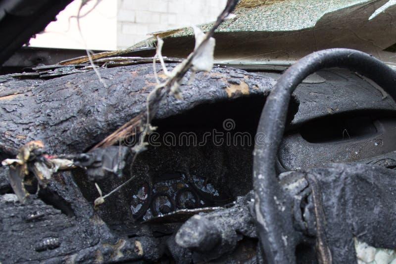 在火以后的客舱,部分地被烧在汽车下的零件 库存照片