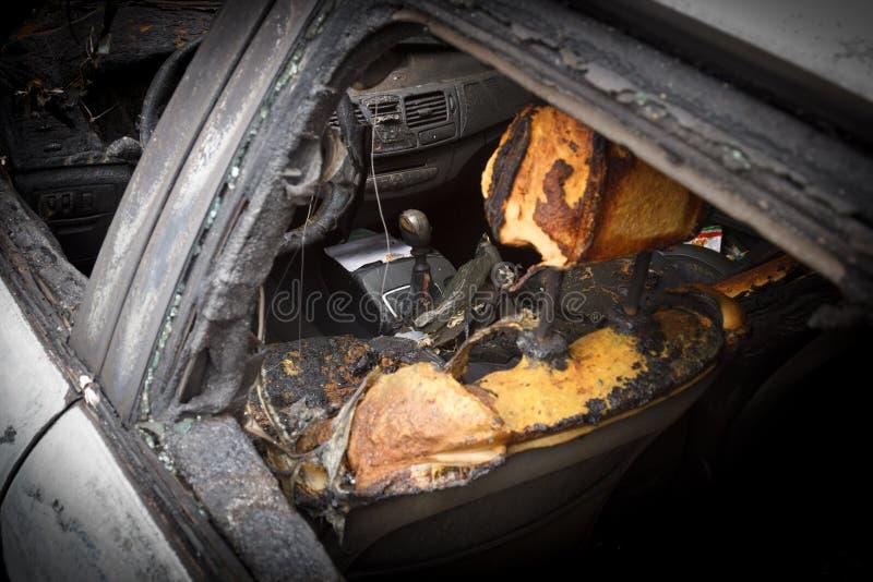 在火以后的客舱,部分地被烧在汽车下的零件 图库摄影