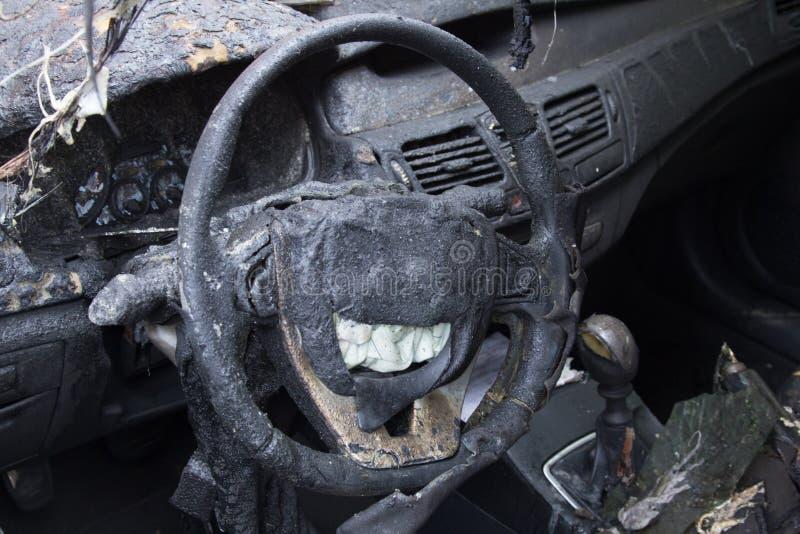 在火以后的客舱,部分地被烧在汽车下的零件 免版税库存照片