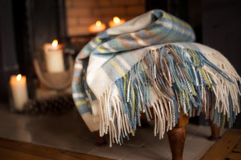 在火地方附近的舒适格子呢毯子有被点燃的蜡烛的 免版税库存图片