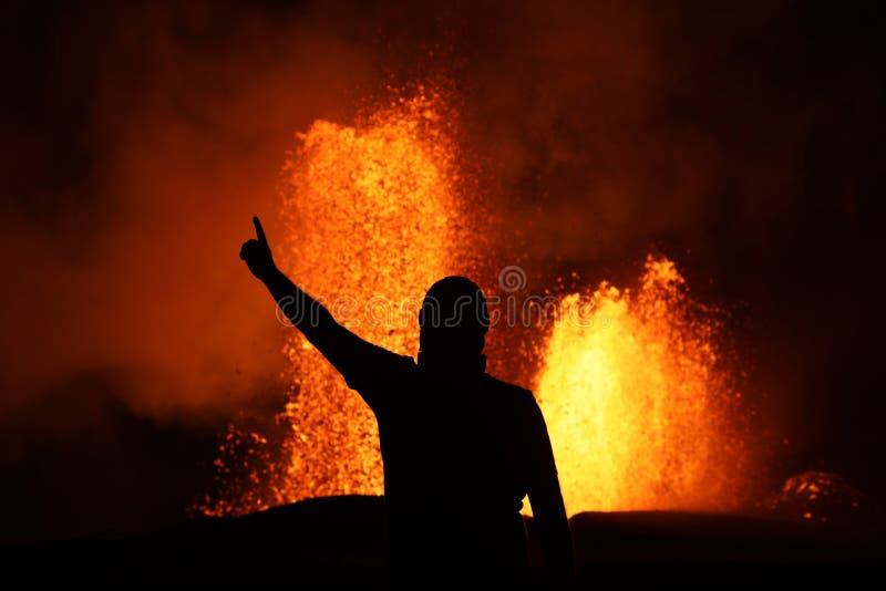 在火山爆发的熔岩喷泉的前面胜利姿势 库存图片