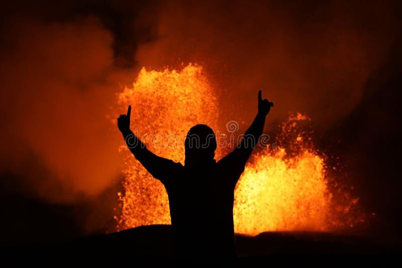 在火山爆发的熔岩喷泉的前面胜利姿势 库存照片