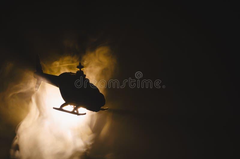 在火日落天际的直升机 战争概念 飞行直升机火backgroung作用军事场面  装饰 库存图片