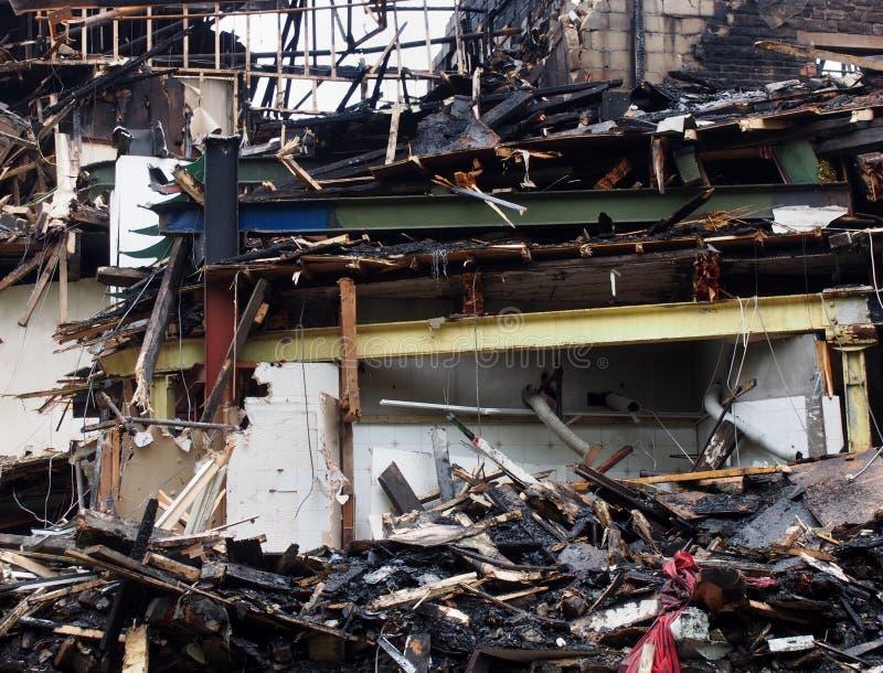 在火毁坏的一个倒塌的大厦的黑被烧的残骸木材和钢粱 库存照片