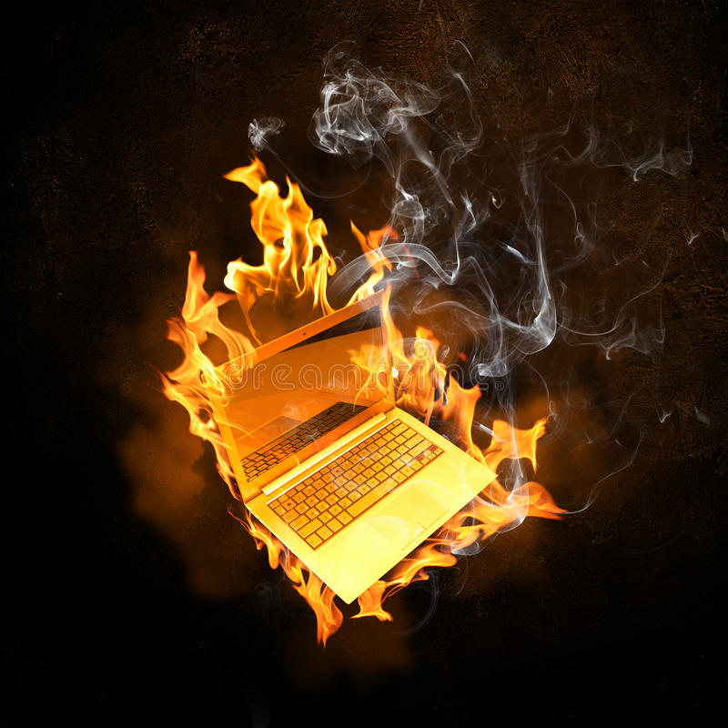 在火火焰的膝上型计算机 库存图片