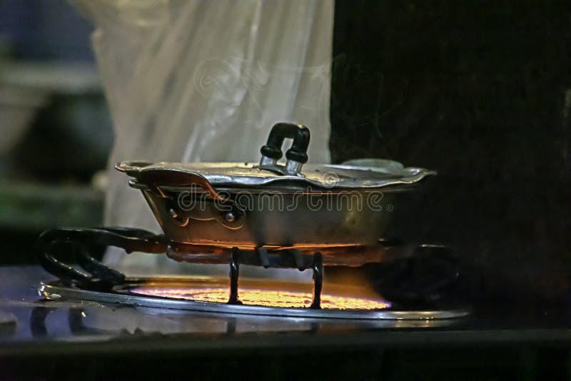 在火炉的不锈钢平底锅与黄色火焰 免版税库存图片