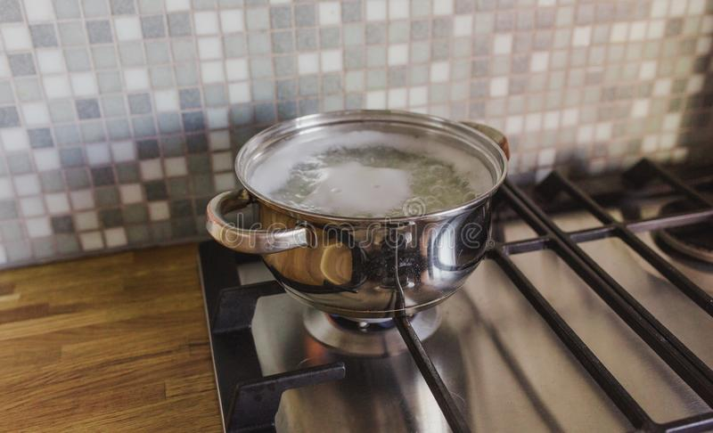 在火炉的平底深锅在一个木桌面的背景的厨房里 库存图片