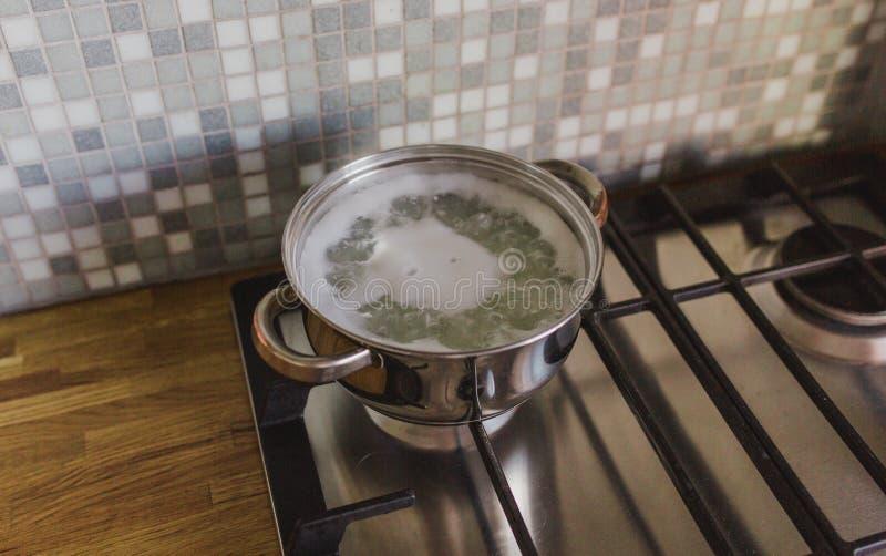 在火炉的平底深锅在一个木桌面的背景的厨房里 免版税库存照片