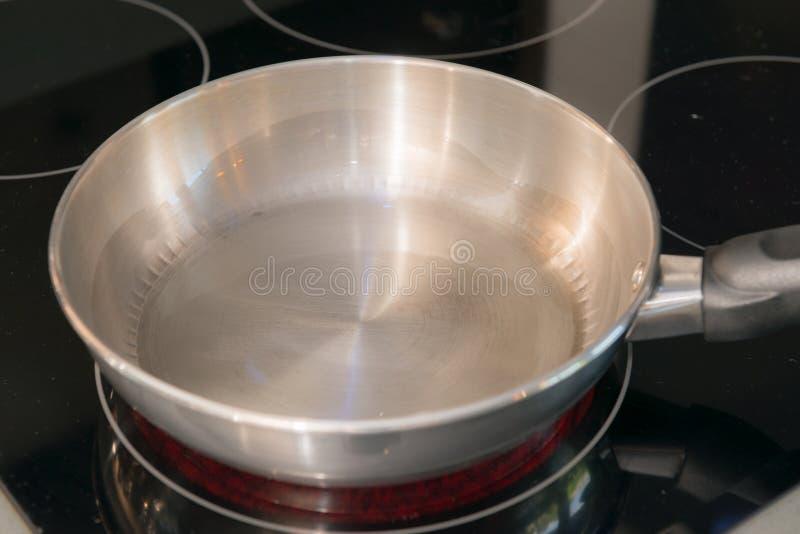 在火炉的空的不锈钢平底锅 库存图片