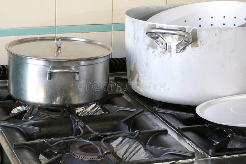 在火炉的罐在公司军用餐具的工业厨房里 免版税库存图片