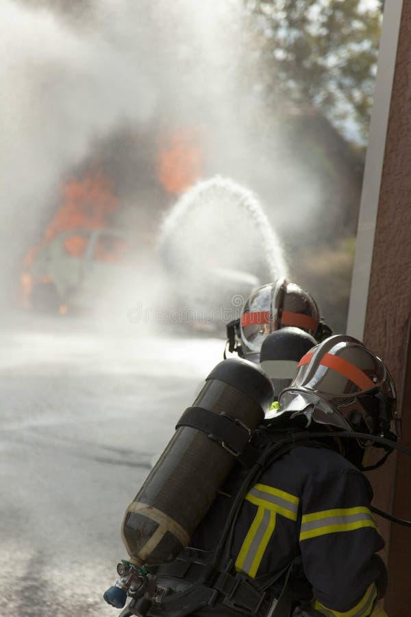 在火烧伤火焰和两名消防队员旅团的汽车与盔甲 免版税库存图片