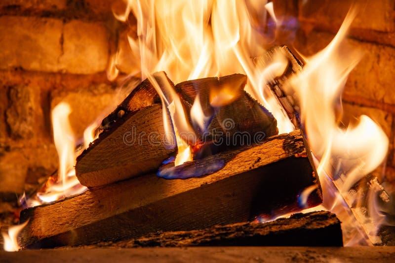 在火烧伤的木柴燃烧在壁炉 砖烤箱给热和热从被烧的日志 燃烧的煤炭和火焰 库存照片