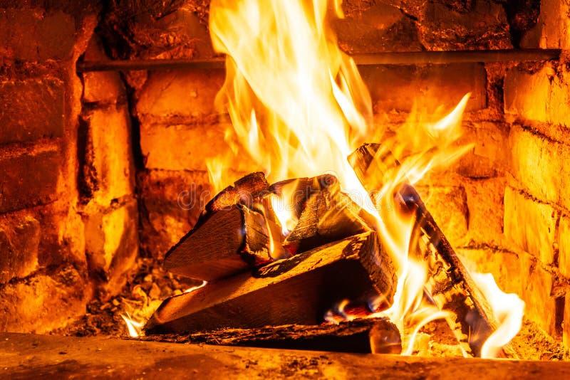 在火烧伤的木柴燃烧在壁炉 砖烤箱给热和热从被烧的日志 燃烧的煤炭和火焰 免版税库存照片