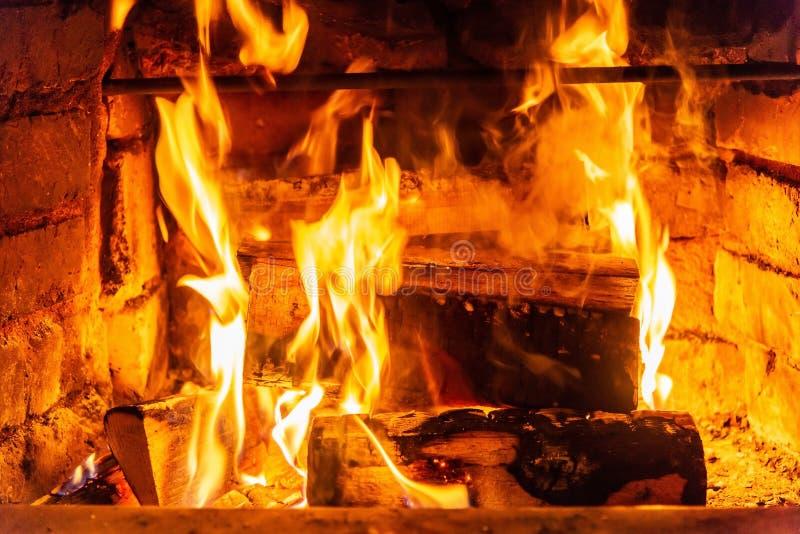 在火烧伤的木柴燃烧在壁炉 砖烤箱给热和热从被烧的日志 燃烧的煤炭和火焰 免版税库存图片