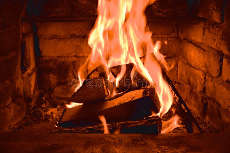 在火烧伤的木柴燃烧在壁炉 砖烤箱给热和热从被烧的日志 燃烧的煤炭和火焰 库存图片