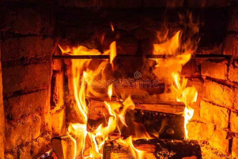 在火烧伤的木柴燃烧在壁炉 砖烤箱给热和热从被烧的日志 燃烧的煤炭和火焰 免版税图库摄影