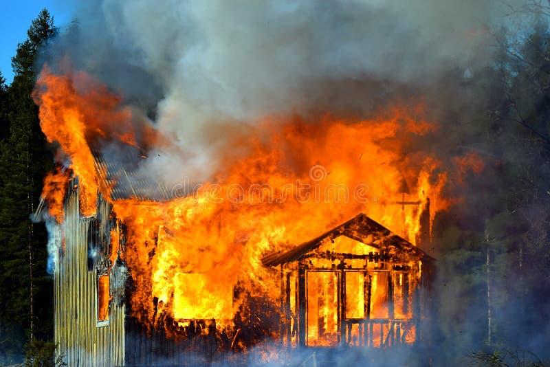 在火焰完全地吞噬的议院 库存照片